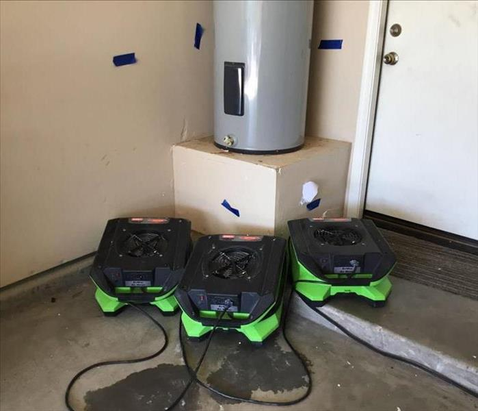 SERVPRO's Equipment Extracting Water In Garage