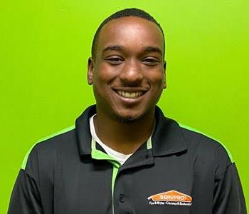 Male employee with black shirt smiling in front of a green background