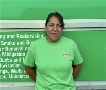 Female employee with black SERVPRO shirt smiling in front of a green background