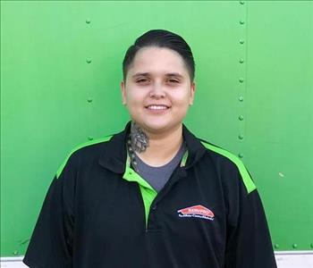 Female SERVPRO employee with short hair smiling in front of a green background