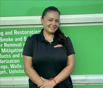 Female employee with dark hair smiling in front of a green background