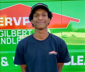 Male employee with SERVPRO hat smiling in front of a green background