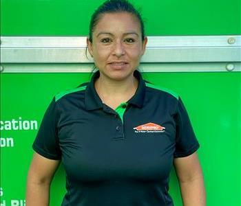 Female SERVPRO employee smiling in front of a green background